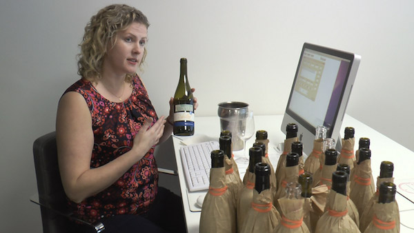 Lady holding bottle of wine next to computer